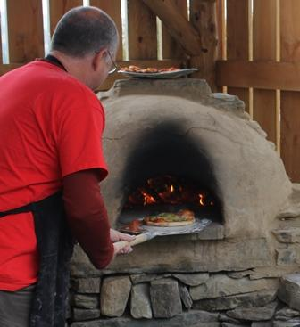 putting pizza into a clay oven